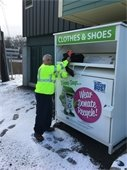Town Foreman Frank Giordano placing old clothes in Town's Textile Bin