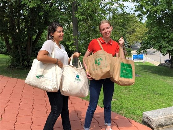 Summer Interns Adriana Alverado and Lily Shein with reusable bags that will be distributed to residents