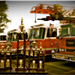 A line of trophies in front of a row of fire trucks.
