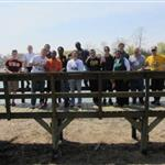 A group of people standing on a boardwalk for a photo.